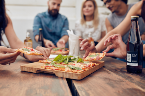 A group of people sitting at a table sharing pizza and drinks together.